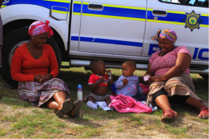 Khayelitsha residents take a break outside the Commission's public hearings, picture: Shae Herrmann