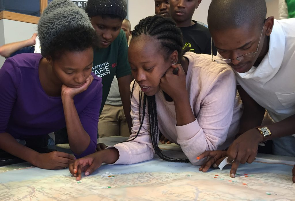Equal Education leaders left to right: Whitney Cele, Nombulelo Nyathela (centre) and Bayanda Mazwi tracing their personal histories on a large map of South Africa