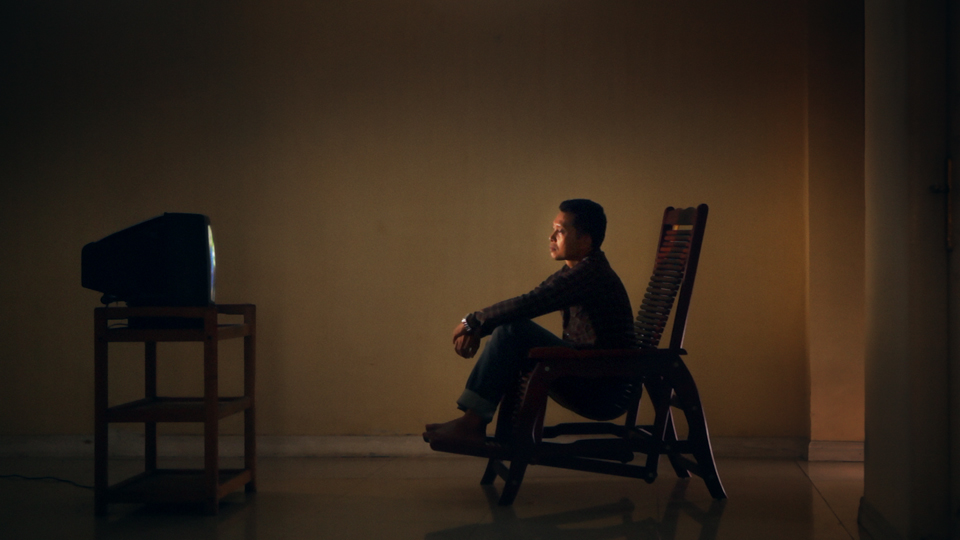 With profound sadness, Adi watches footage of interviews conducted by Joshua Oppenheimer with perpetrators of the 1965-66 Indonesian genocide in Drafthouse Films' and Participant Media's The Look of Silence. Courtesy of Drafthouse Films and Participant Media.